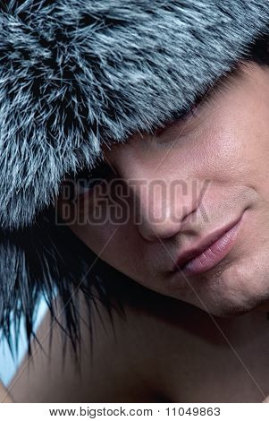 Close-up portrait of handsome young man wearing fluffy hat