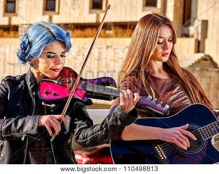 Music street performers two girls violinist with blue hair playing  aganist city outdoor.
