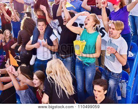 Sport fans eating popcorn  and singing on tribunes. Group emotion people.