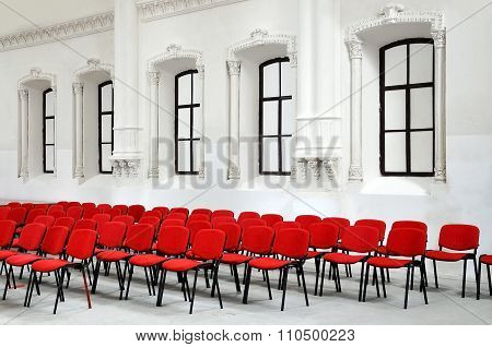 Many red chairs on background of white ancient wall