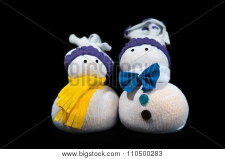 Handmade two snowmen sewn from fabric isolated on black background