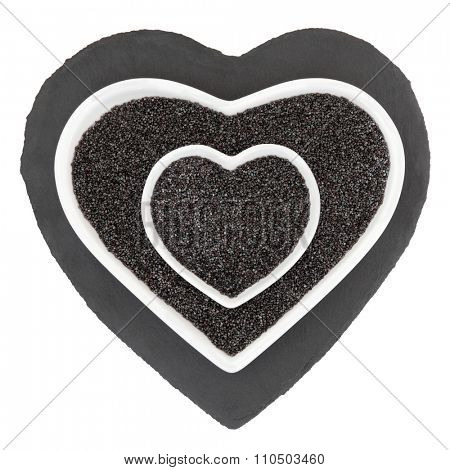 Poppy seed health food in heart shaped porcelain bowls on slate over white background.
