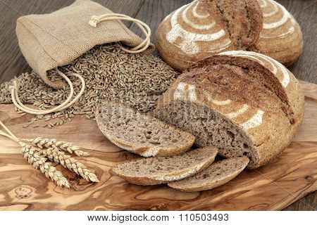 Fresh baked homemade rye bread on an olive wood board with wheat sheaths and grain in a hessian bag over  oak background.