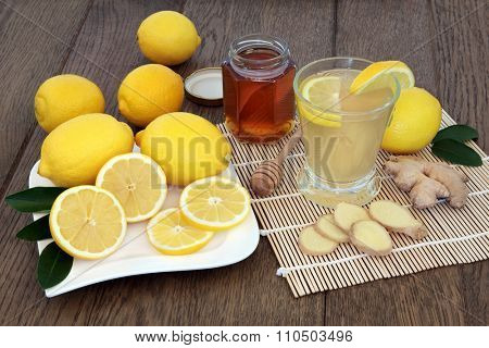 Natural cold and flu remedy drink in glass with fresh ginger, lemon and honey over oak background.