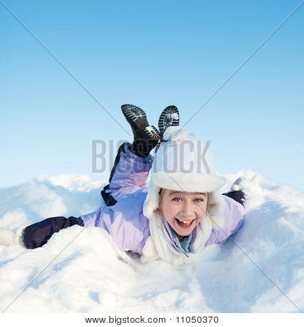 Funny little girl sliding in the snow
