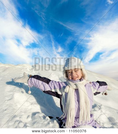 Happy little girl sitting in the snowy field