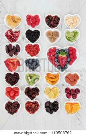 Fruit superfood background selection with fruits high in antioxidants, vitamin c and dietary fibre in heart shaped bowls over distressed white wood.