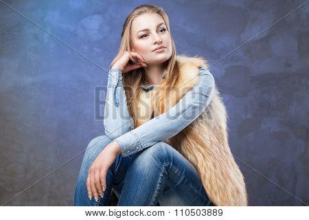 elegant woman sits wearing blue jeans and fur vest