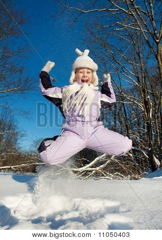 Funny happy girl jumping in the snow