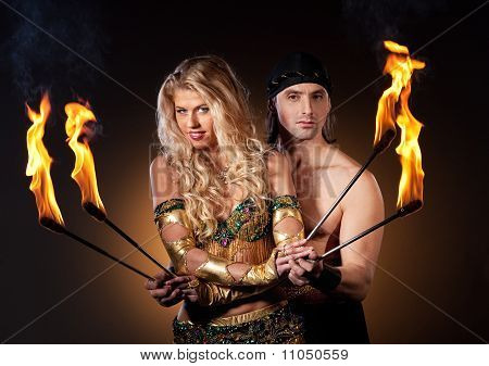 Couple performing fire show with torches