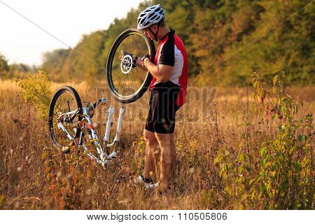 Man cyclist repairing a bike  against green nature