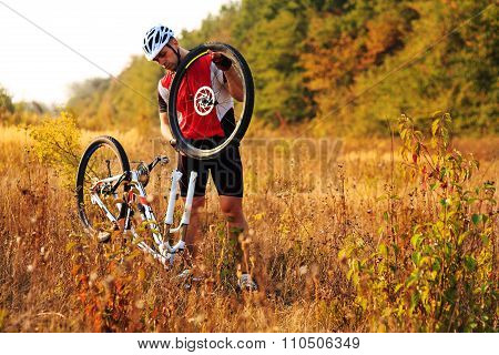 Man cyclist repairing a bike  against green nature