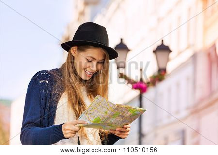 Cute beautiful girl with hat holding city map