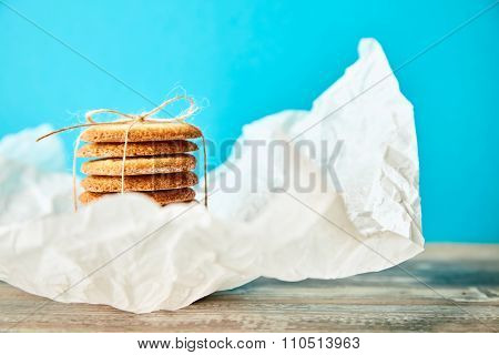 Stack Of Cookies Tie With Rope On Blie Background In White Blurred Paper