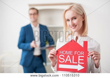 Cheerful young woman is presenting her house