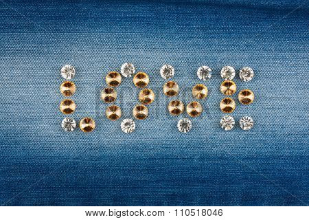 Word love made of rhinestones on denim fabric
