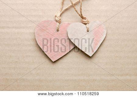 Couple of cardboard cut hearts against striped cardboard sheet