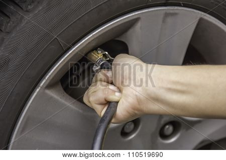 Hand Filling Air Into A Car Tire, Close Up.