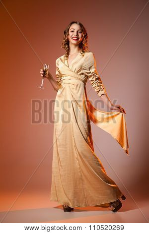 Elegant Woman in Golden Dress with wineglass