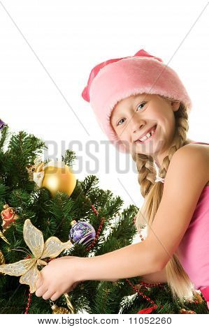 Little Santa girl decorating the Christmas tree