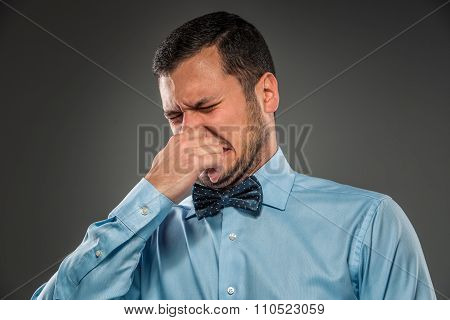 Young man - disgusted expression closing his nostrils with finge