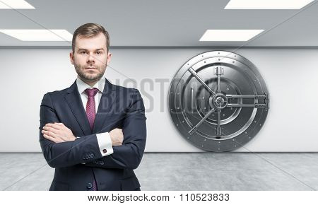Businessman In Front Of Big Locked Metal Safe, Bank Depository