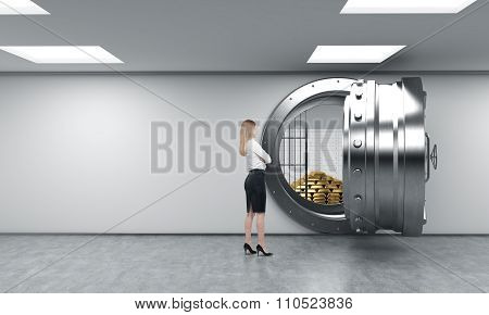 Woman In Front Of Unlocked Safe With Pyramid Of Gold