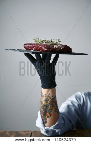 Tattoed Hand In Black Glove Holds Stone Plate With Steak Ready To Cook