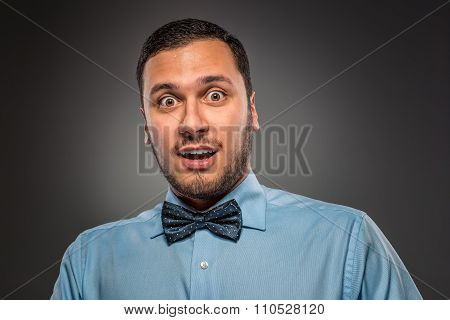 Portrait young man in blue shirt, looking with amazement