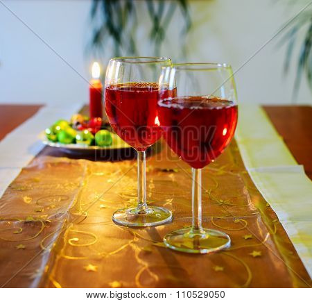 Wine Glasses With Red Wine And Christmas Decoration