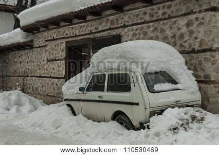 Snow-drift cover front door and car in winter at Bansko, Bulgaria