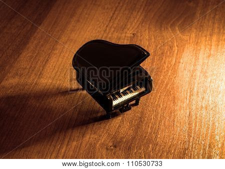 Miniature Model Of Black Grand Piano With Shadow On Wooden Table Warm Filtered