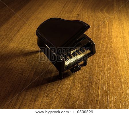 Miniature Model Of Black Grand Piano With Shadow On Wooden Table Filtered