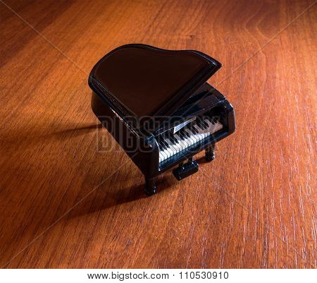 Miniature Model Of Black Grand Piano With Shadow On Red Wood Table