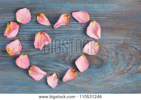 Pink rose petals imaging heart shape with two petals inside on blue wooden board