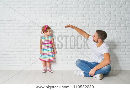 Concept. Dad Measures Growth Of Her Child Daughter At A Wall