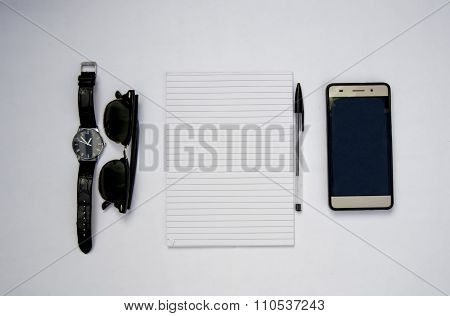 Kit with watch, sunglasses, pen, smartphone and a notebook for creative people, writers and designer