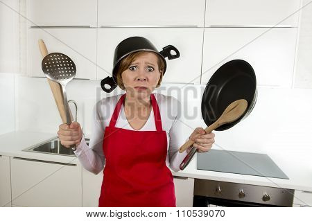 Young Attractive Home Cook Woman In Red Apron At  Kitchen Holding Pan And Household With Pot On Her