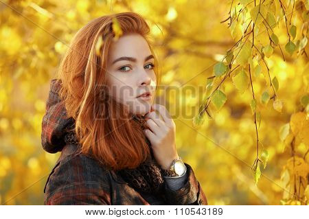 Outdoors portrait of young beautiful redhead woman in scarf and jacket on yellow autumn foliage back