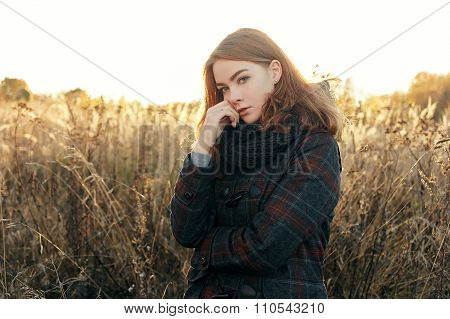 Outdoors noon portrait of thoughtful young beautiful redhead woman in scarf and jacket on faded mead