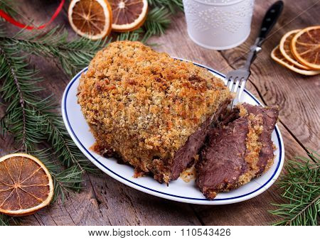 Roasted beef with bread crust sliced on plate