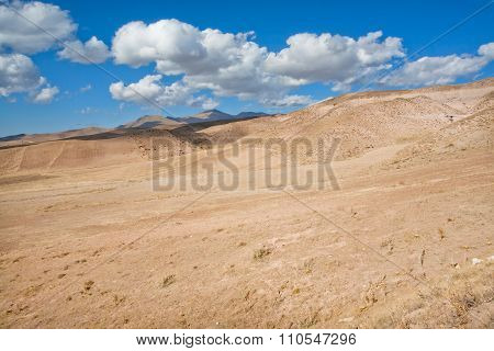 White Clouds Float Over The Arid Landscape In A Valley With A Dried Soil