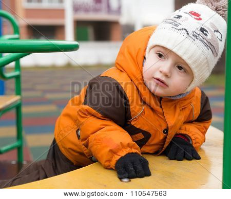 The Little Boy In A Jacket And A Warm Cap, At A Playground In Autumn Day, Leaned The Elbows A Stomac