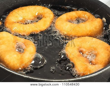 Closeup Of Doughnuts Boiling In Kettle Of Oil