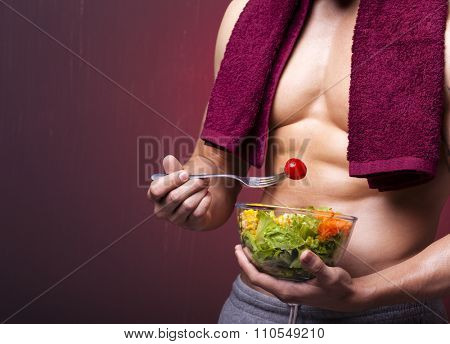 Muscular man holding a bowl of salad on grunge background