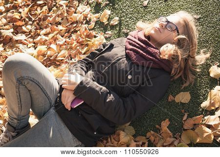 Beautiful Caucasian Blond Teenage Girl Laying In Park