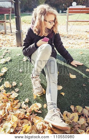 Beautiful Blond Teenage Girl In Glasses Sitting In Park