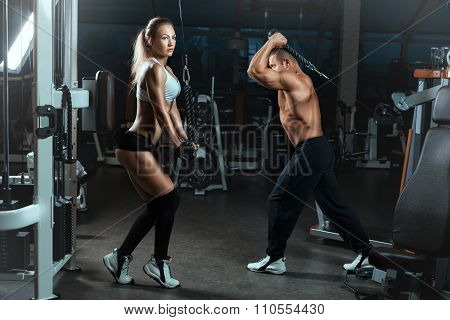 Girl And  Man Go Sports Hall With Machines For Bodybuilders.