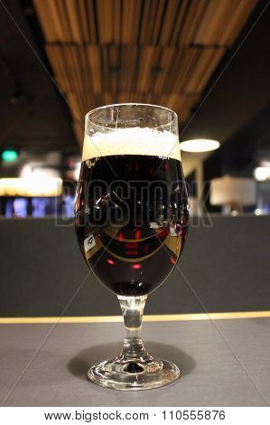 Glass of dark beer on the bar at irish pub