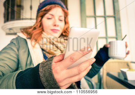 Pretty Young Woman Holding Mobile Phone And Tea Cup Sitting At Cafe